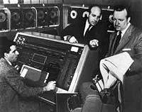 Remington Rand employees, Harold E. Sweeney (left) and J. Presper Eckert (center) demonstrate the U.S. Census Bureau's UNIVAC for CBS reporter Walter Cronkite (right).